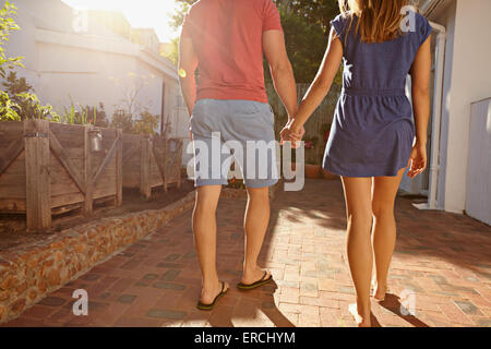 Cropped shot of young couple walking towards their house together. Rear view of couple in backyard taking walk on - Stock Photo