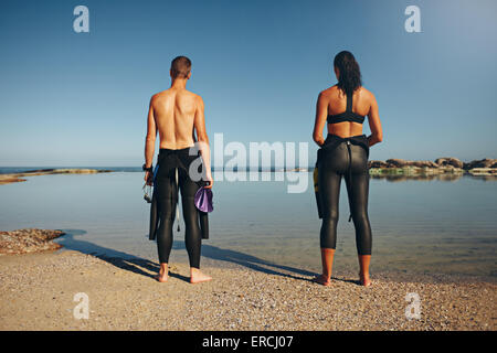 Rear view of young athletes standing on lake preparing for triathlon. Man and woman preparing for a race wearing - Stock Photo