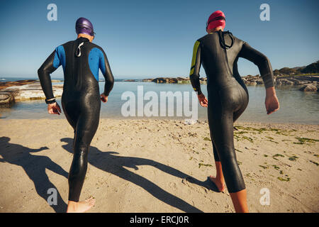 Rear view of triathlon participants ready to start of the race. Triathletes standing at the start line by the lake, - Stock Photo