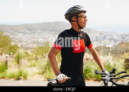 Young man wearing cycling helmet and sunglasses standing with his bicycle looking away. Male cyclist training on - Stock Photo