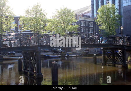Lots of bikes parked on an old cast iron bridge at Nieuwe Achtergracht canal, Amsterdam, The Netherlands - Stock Photo