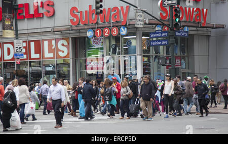 There are always crowds on the street at 7th Avenue and 34th Street in NYC. - Stock Photo