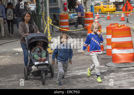 Children with nanny on their way home after school in the highly urban Tribeca neighborhood in Manhattan. - Stock Photo