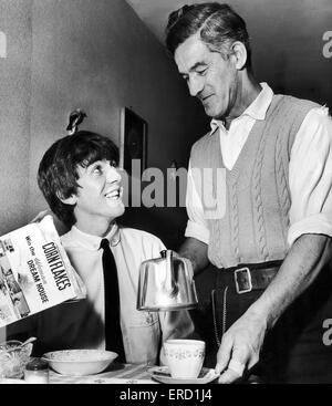 George Harrison, sits down to breakfast with his father, Harold Hargreaves Harrison, at home in Liverpool, where - Stock Photo