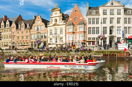 Tour boat passes buildings in Graslei, the quay on the east bank of the River Lys, in the historic centre of Ghent, - Stock Photo