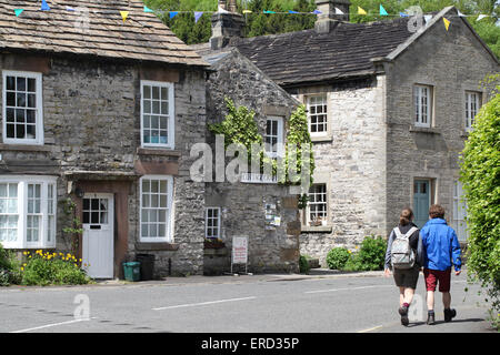 Couple walking through the Peak District village of Ashford in the Water near Bakewell - Stock Photo