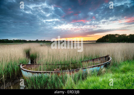 Beautiful stunning sunrise over an old fishing boat in reeds at Poole harbour in Dorset - Stock Photo