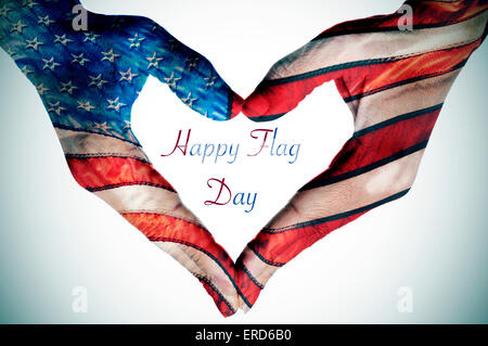the text happy flag day written in the blank space of a heart sign made with the hands of a young woman patterned - Stock Photo