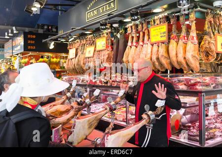 Serrano ham at La Boqueria market, Barcelona, Spain - Stock Photo