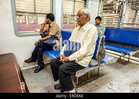 Mumbai India Asian Churchgate Railway Station Western Line train public transportation riders passengers sitting - Stock Photo