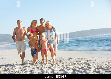 Extended Family Walking Along Sandy Beach By Sea - Stock Photo