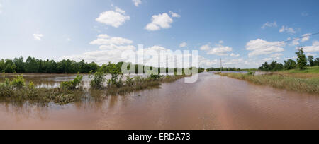 Panorama of a rural road completely inundated with flood waters, with pasture land on the left under water after - Stock Photo