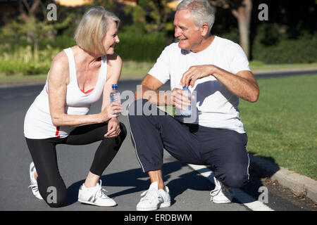 Senior Couple Resting And Drinking Water After Exercise - Stock Photo
