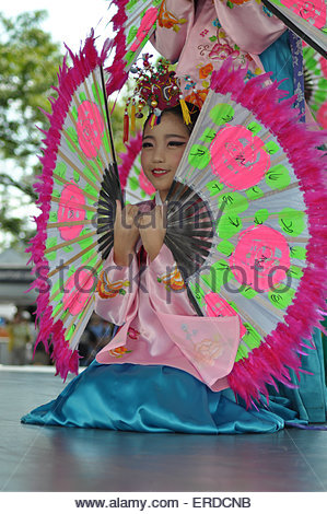 Korean dancers: Asian girl in traditional costume with large fans dancing on stage of music show at the Redpath - Stock Photo