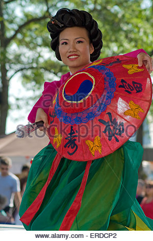 Korean dancer woman in a colored dress with hat and a fan in the hands of the dancing on stage - Stock Photo