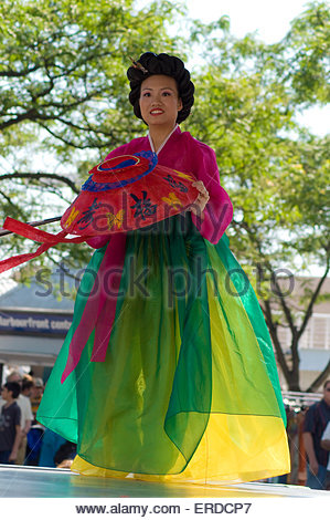 Korean dancer woman in colored dress and hat in his hand standing on the stage. The people and trees on blurry background - Stock Photo