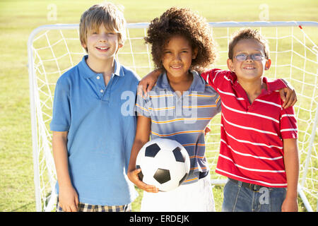 Young Boy With Soccer Ball Standing By Goal - Stock Photo