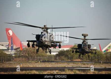 A pair of AH-64D Apache Longbow helicopters lift off on a mission in support of  exercise Angel Thunder 2013. - Stock Photo