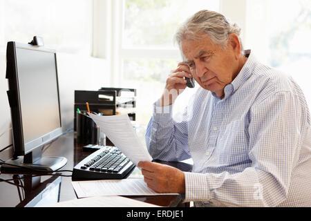 Senior Hispanic man working on computer at home - Stock Photo
