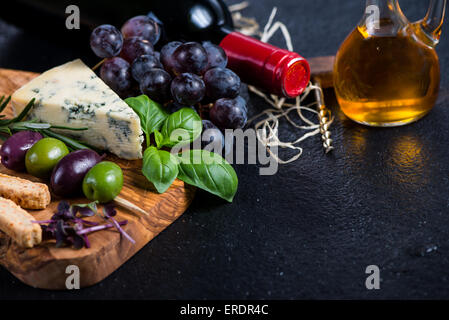 Tapas board with cheese,olives,grapes and red wine,food border background - Stock Photo