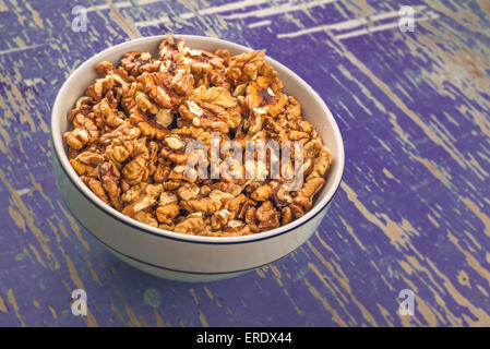 Peeled Walnuts in Ceramic Bowl on Purple Rustic Wood Plank Background - Stock Photo