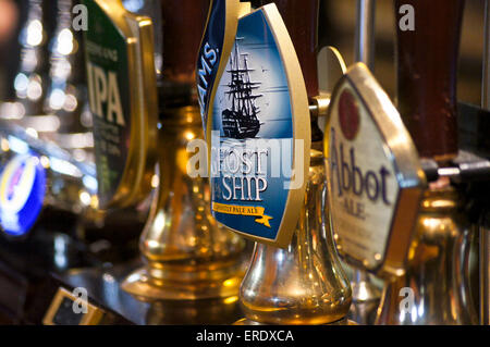 Real ale handpumps and pump clips on a pub bar- Adnams Ghost Ship, Greene King IPA and Abbot Ale - Stock Photo