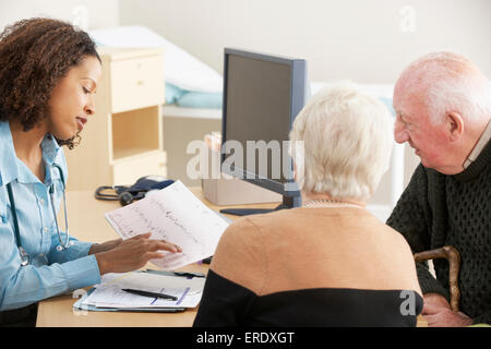 Young female Doctor talking to senior couple - Stock Photo