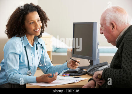 Young female Doctor with senior male patient - Stock Photo