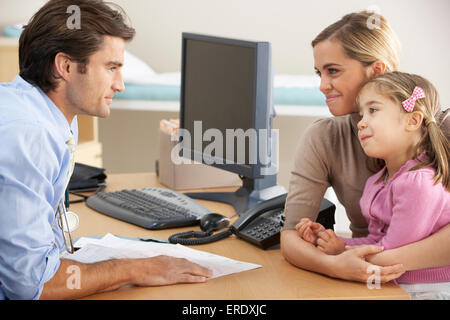 Doctor talking to mother and child - Stock Photo