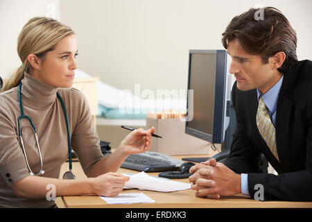 Female Doctor talking to businessman patient - Stock Photo