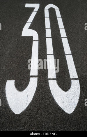 Speed-limit sign 30 kph on an asphalt road, Germany - Stock Photo