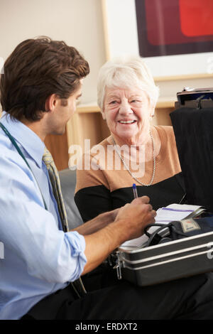 Doctor visiting senior woman at home - Stock Photo