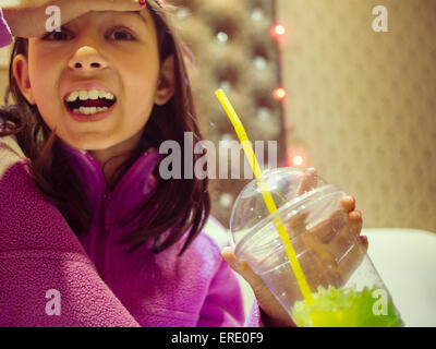 Mixed race girl with brain freeze drinking frozen drink
