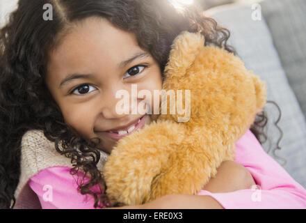 Mixed race girl hugging teddy bear on sofa - Stock Photo