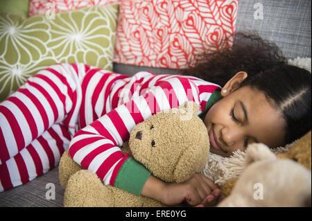 Mixed race girl sleeping on sofa - Stock Photo