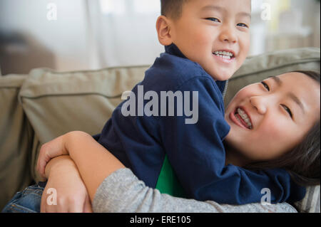 Asian brother and sister playing on sofa - Stock Photo