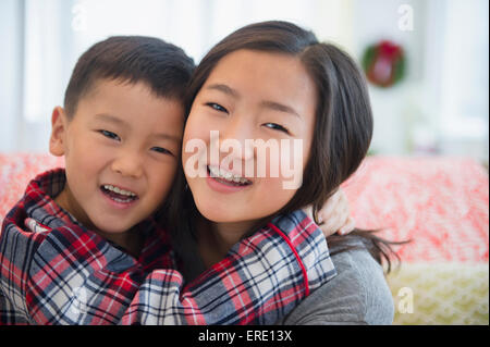 Asian brother and sister hugging - Stock Photo