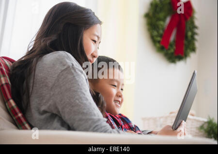 Asian brother and sister using laptop on sofa - Stock Photo