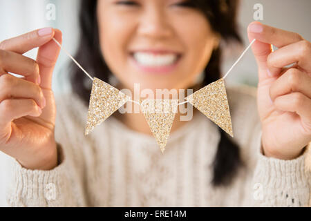 Pacific Islander woman holding miniature banner decoration - Stock Photo