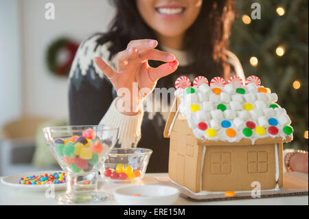 Pacific Islander woman decorating gingerbread house - Stock Photo