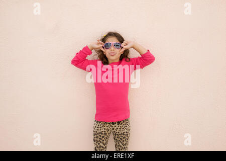 Hispanic girl wearing sunglasses and sticking out tongue - Stock Photo