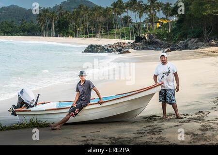 Friends standing near boat on beach - Stock Photo