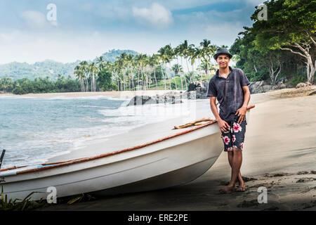 Hispanic man standing near boat on beach - Stock Photo