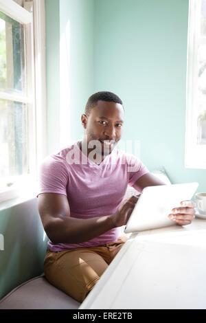 Black man using digital tablet at table - Stock Photo