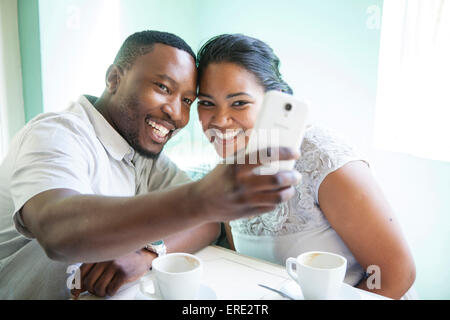 Smiling couple taking cell phone selfie - Stock Photo