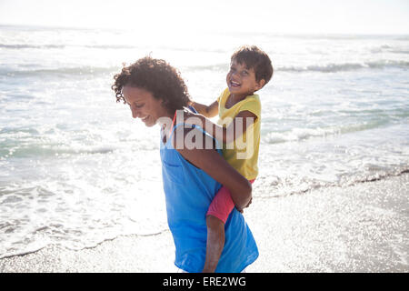 Mixed race mother carrying daughter piggyback on beach - Stock Photo