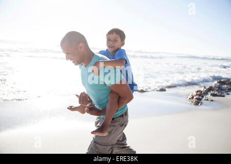 Mixed race father carrying son piggyback on beach