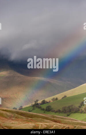 Rainbow in spring showers, over Cautley Crag in the Howgills near Sedbergh, Cumbria, UK. - Stock Photo