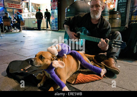 Homeless man busking and playing guitar in Soho with his dog. - Stock Photo