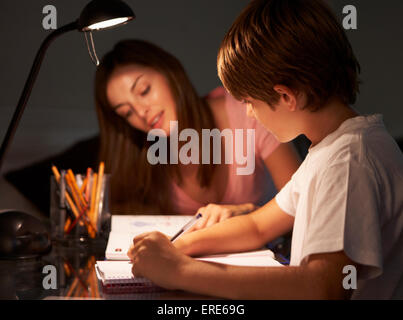 Teenage Sister Helping Younger Brother With Studies At Desk In Bedroom In Evening - Stock Photo